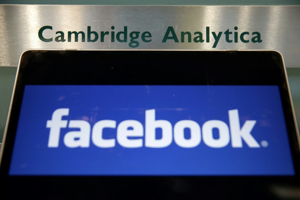 Le logo de Facebook affiché sur un ordinateur portable devant la plaque d'entrée de la société britannique Cambridge Analytica à Londres, le 21 mars 2018 © AFP Daniel LEAL-OLIVAS